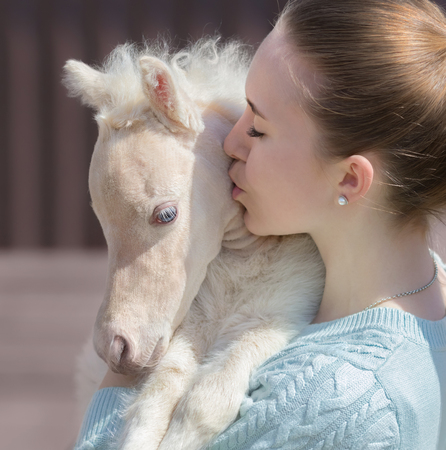 miniature breed: Young cute woman kissing beautiful miniature cream foal. Unique breed  is American Miniature Horse. Foal is one month of birth. Concept about animals and people.