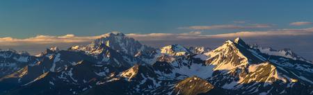 First rays of raising sun on mountain peak. Mounts Zakzan-Syrt and Pshish. Greater Caucasus Mountain Range. Karachay-Cherkessia. Russia.