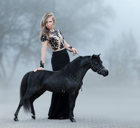 Beautiful woman and black American miniature horse in autumn park in sunrise fog.