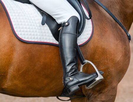 Close up image of jockey riding boot in the stirrup. Rider on bay sport horse.  스톡 콘텐츠