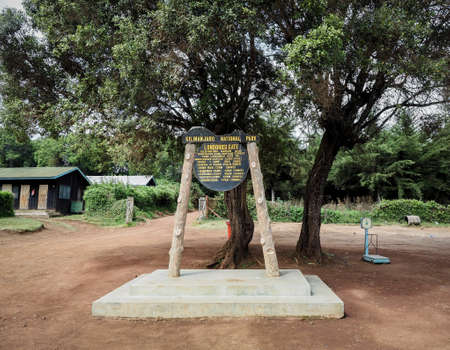 the base camp sign post. guides porters and sherpas carry heavy sacks as they ascend mount kilimanjaro