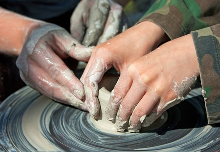 Potter hands guiding a child to create pottery photo