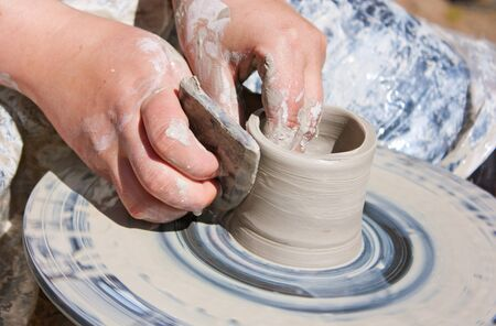 Potter hands working on pottery wheel