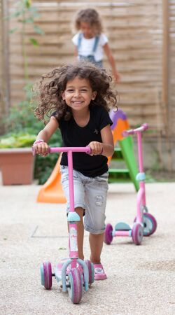 Smiling girl playing with a scooter  photo