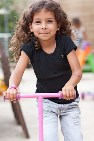 Smiling girl playing with a scooter