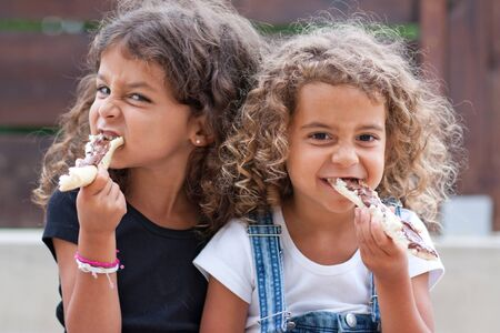 twin sister: Sisters crunching heartily into a slice of bread with chocolate