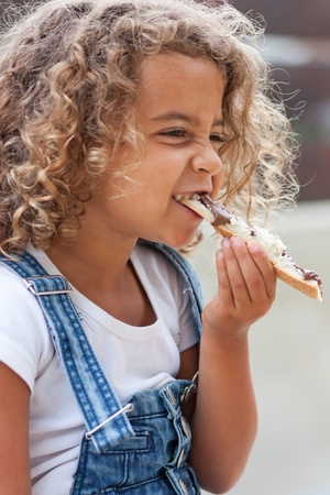 Girl crunching heartily into a slice of bread with chocolate