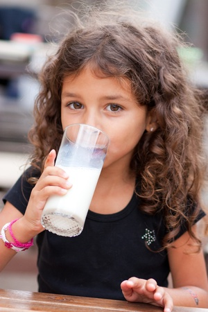 Cute little girl drinking a glass of milk