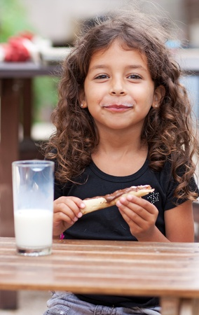 Girl eating a slice of bread and drinking a glass of milk