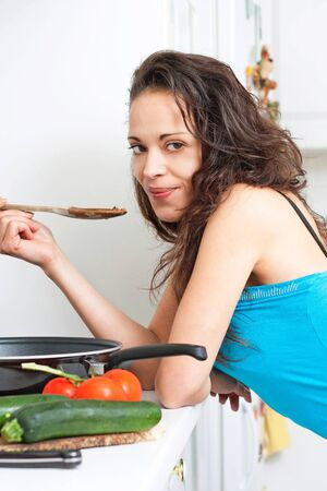 Pretty young woman tasting her cooking Stock Photo - 13664440