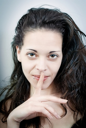 Sensual young woman with her finger on her lips photo