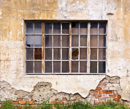 dilapidated wall: A large window with broken panes on the wall of a dilapidated old building Stock Photo
