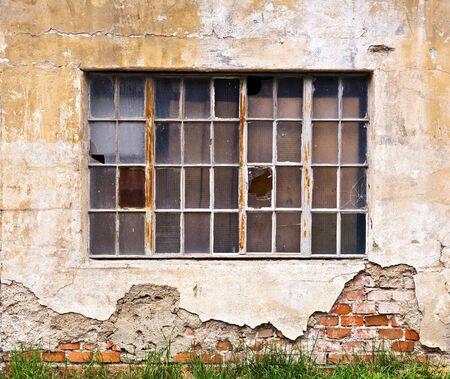 pared rota: Una gran ventana con los cristales rotos en la pared de un viejo edificio en ruinas