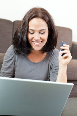 costumer: Beautiful woman in front of her laptop and holding a credit card