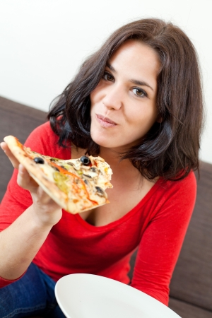 Portrait of a young woman holding and eating a pizza photo
