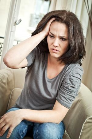 femme triste: Femme avec sa main dans les cheveux, l'air inquiet ou souffrant