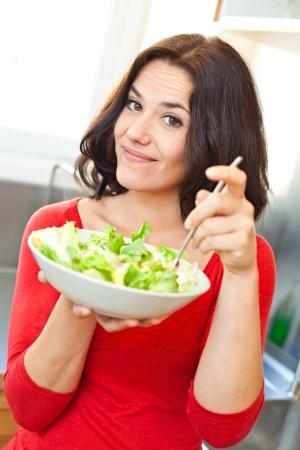 ni�a comiendo: Mujer joven de pie comiendo un plato de verduras