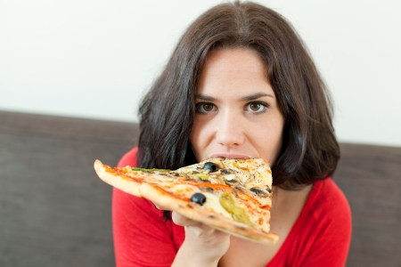 Closeup portrait of a young woman eating a pizza