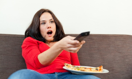 Brunette with a pizza, watching tv and looking amazed photo