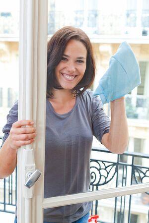 femme nettoyage: Sourire, femme, nettoyage des vitres de son salon