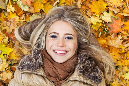 Closeup portrait of a young smiling woman surrounded by autumn leaves photo