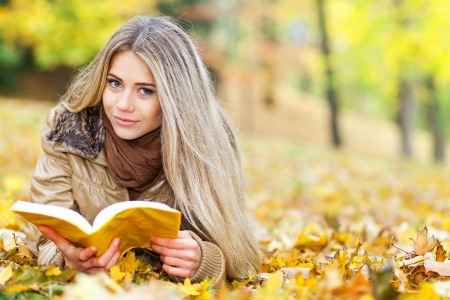 Beautiful woman lying in a park, reading and smiling photo