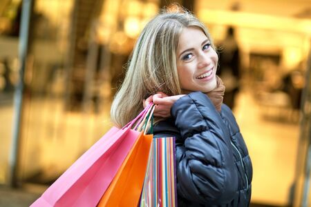 costumer: Young smiling woman walking on the street and enjoying shopping Stock Photo