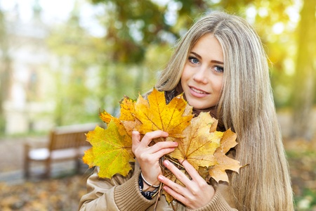 Young woman holding leaves in a park in autumn