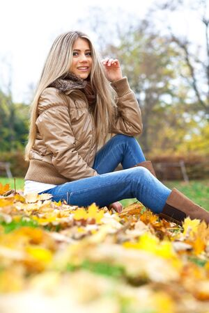Pretty smiling woman in a park in autumn Stock Photo