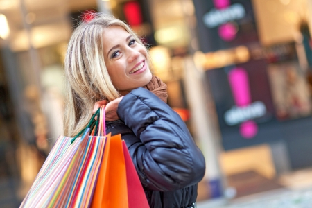 costumer: Young smiling woman walking on the street and shopping