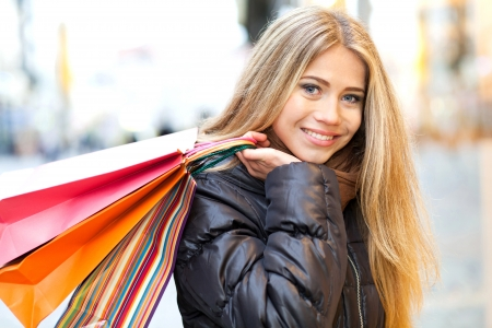 costumer: Young woman in front of a window shop and holding shopping bag Stock Photo