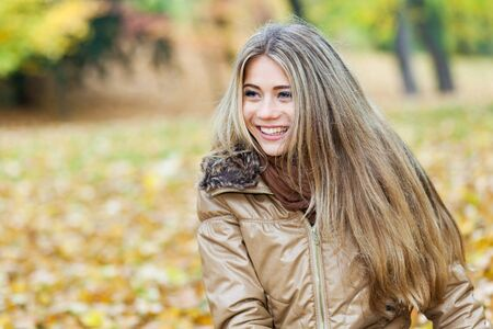 Young smiling woman in a park in autumn photo