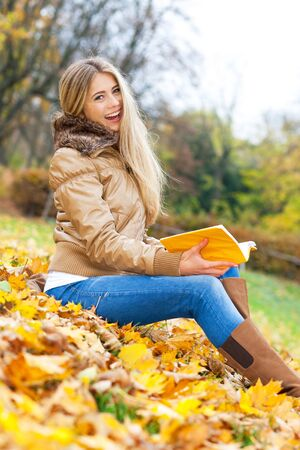 Young woman sitting in a park, holding a book and laughing photo