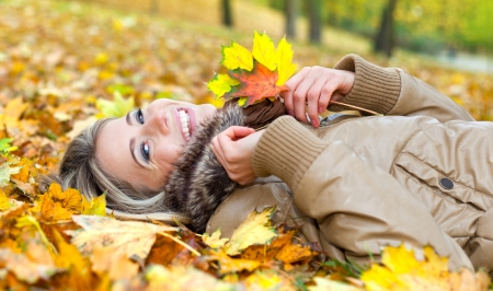Portrait of a nice young woman surrounded by autumn leaves