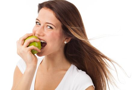 Young woman biting a green apple, isolated on white photo