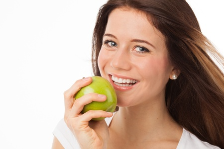 Close up portrait of a beautiful woman eating a green apple, isolated on white Standard-Bild
