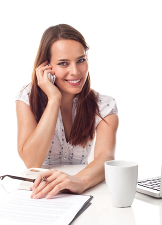 Beautiful young woman phoning, working in front a laptop, isolated on white  Stock Photo