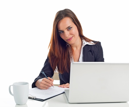Young business woman working in front a laptop, writing on a paper, isolated on white