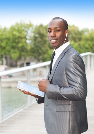 mobile headsets: Portrait of a smiling businessman on the phone with hands-free headset and using electronic tablet Stock Photo