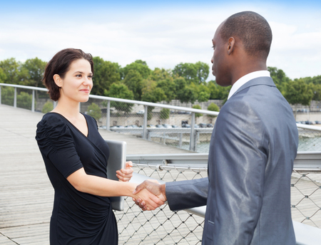 collaborators: Cheerful businesspeople, or businessman and client, handshaking Stock Photo