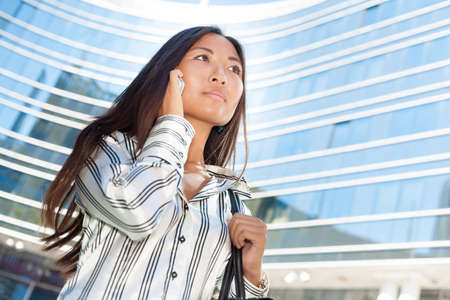 Portrait of a beautiful asian businesswoman walking and using cell phone photo