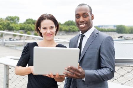 collaborators: Multiethnic collaborators working on laptop, outdoors