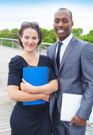 collaborators: Portrait of business collaborators outdoors, woman holding some folders and man holding a laptop Stock Photo