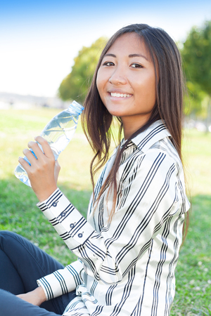 Portrait of an young asian girl in a park with a bottle of water photo