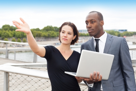 Multi ethnic businesspeople working outdoors with a businesswoman showing something in front of them photo