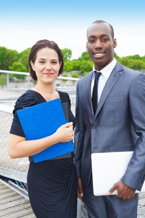 collaborators: Portrait of smiling business collaborators, woman holding some folders and man holding a laptop, outdoors