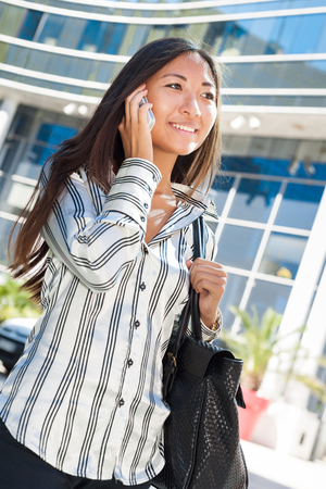 Pretty asian girl walking and talking on cell phone photo