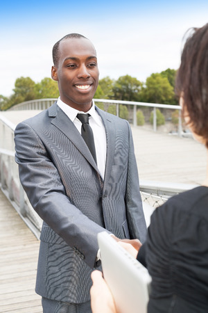 Smiling businessman and businesswoman or client handshaking photo