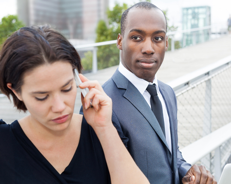 collaborators: Multi ethnic business people working outdoors, woman phoning