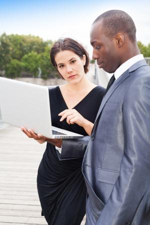 collaborators: Multiethnic businesspeople working on laptop, outdoors